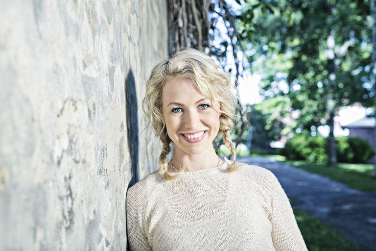 Kuvassa vaaleahiuksinen nainen nojaa seinään
