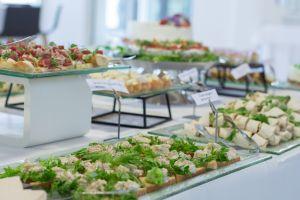 Ruoka-annoksia tarjoiluvadeissa pöydällä.