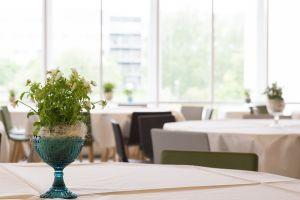 Ruokasalin pöytiä, joissa on kukkakimppuja.