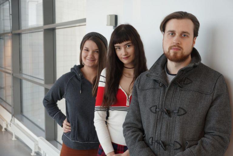 Kaksi nuorta naista ja mies seisovat limittäin seinän vieressä.