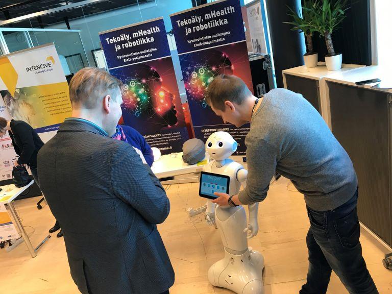 Mies ohjaa puhuvaa robottia sen näytön avulla.