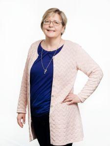Vaalea, silmälasipäinen nainen seisoo hieman sivuttain käsi lanteilla.