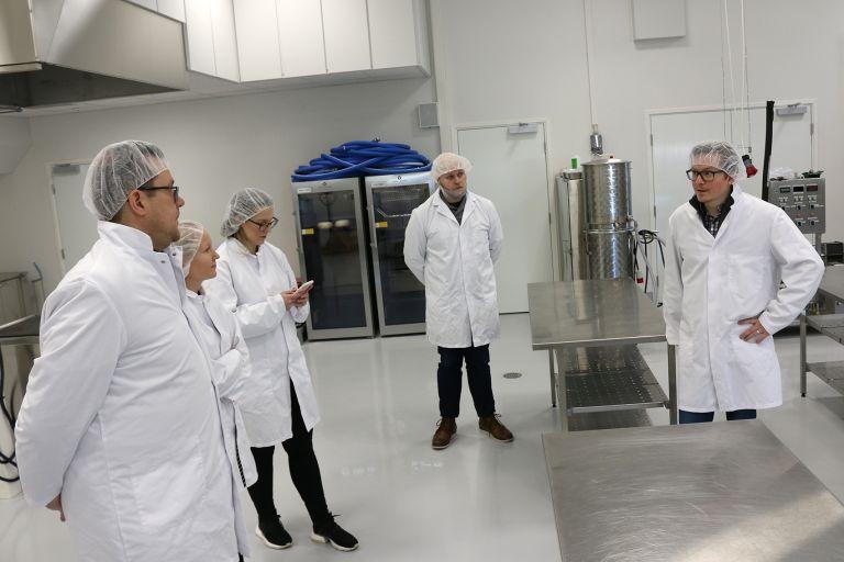 Viisi ihmistä pukeutuneena valkoisiin suojatakkeihin ja päähineisiin seisoo elintarvikelaboratoriossa.