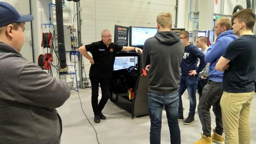 Mies opettaa opiskelijoita autolaboratoriossa.