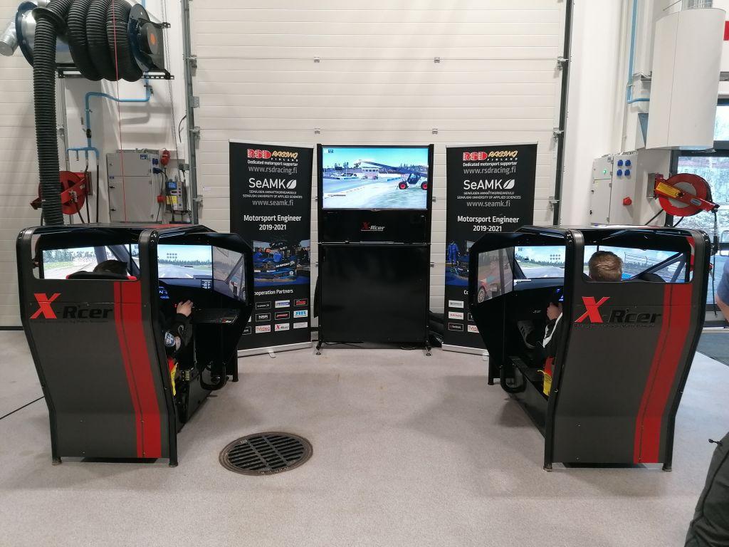 Kaksi opiskelijaa ajaa rallia simulaattoreissa.