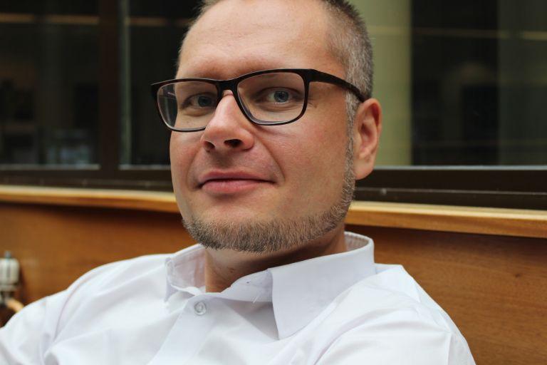 Mies, jolla on silmälasit ja valkoinen paita, istuu ja katsoo kameraan päin.