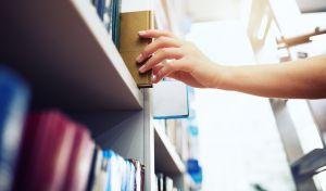 Opiskelija ottaa kirjan kirjaston hyllystä.