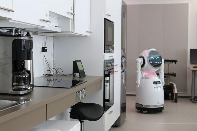 Kuvassa keittiötila, valkoiset kaapistot, kodinkoneita ja niiden vieressä robotti sekä rollaattori.
