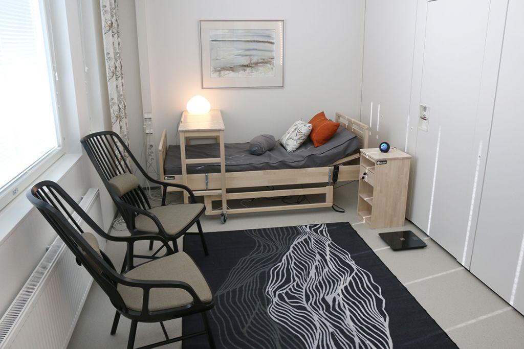 Pieni, vaalea makuuhuone, jossa sänky taka-alalla sekä mattoja ja kaksi mustaa nojatuolia keskellä.