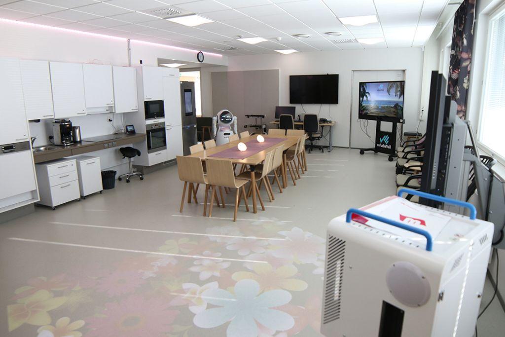 Iso huone, jossa on projektori etualalla, suuri ruokailuryhmä keskellä sekä suuria näyttöjä takaosassa.