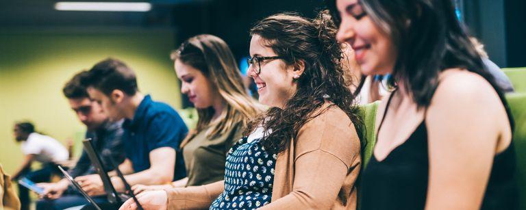 Hymyileviä opiskelijoita luennolla auditoriossa. Opiskelijoilla on sylissään kannettavat tietokoneet./ Smiling students on a lecture in the auditorium. Students have laptops in their laps.