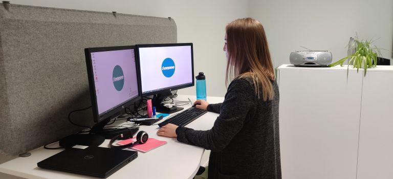 Nainen seisoo työpisteellään. Pöydällä on kaksi tietokoneen näyttöä, joissa on Eepeen logo.