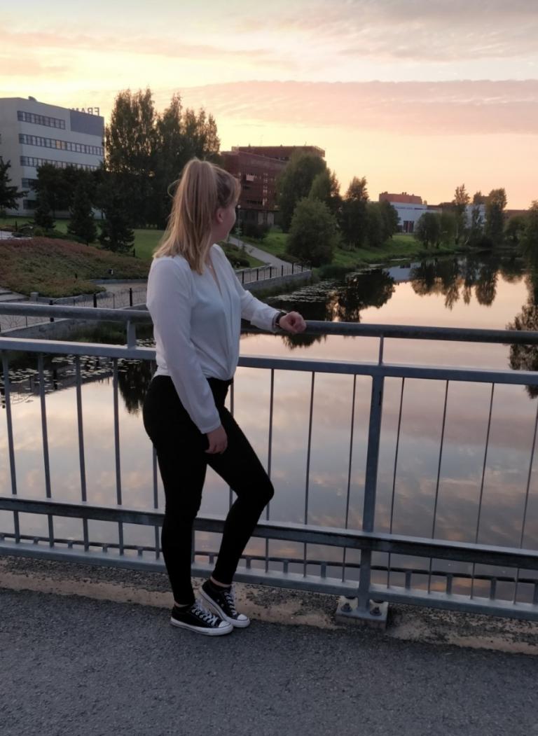 Nainen nojaa sillan kaiteeseen joen yllä auringonlaskun aikaan. Taustalla näkyy kampusalueen rakennuksia joen varrella.