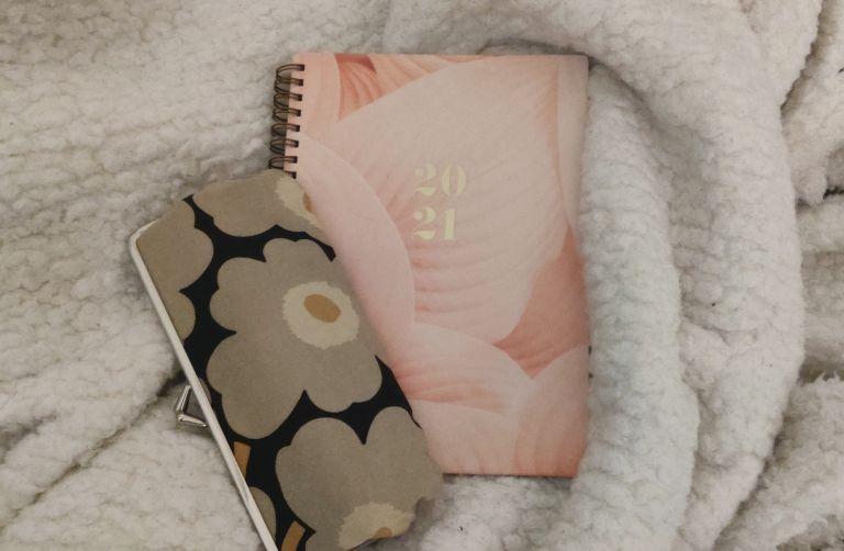 Penaali ja vuosikalenteri sängyn päällä.