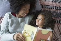Äiti ja lapsi lukevat kirjaa.