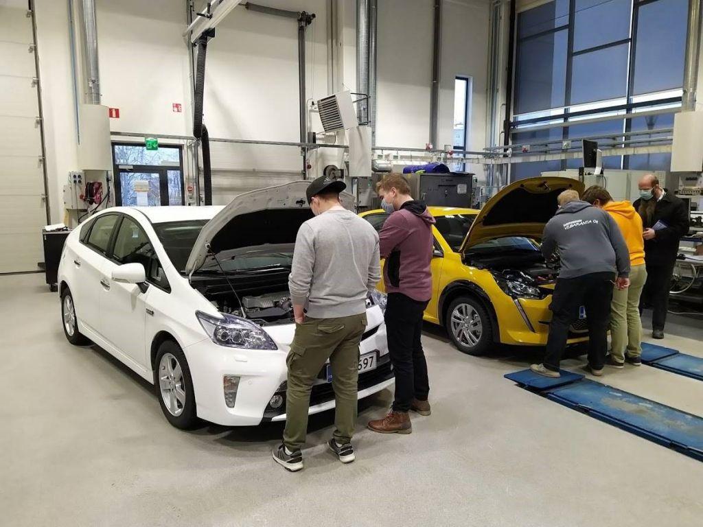 Opiskelijat tutkivat kahta kilpa-autoa autolaboratoriossa.