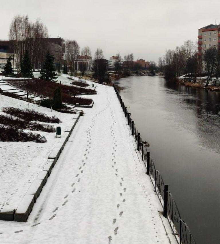 Jalanjäkiä lumessa Frami-kampuksen jokirannassa.