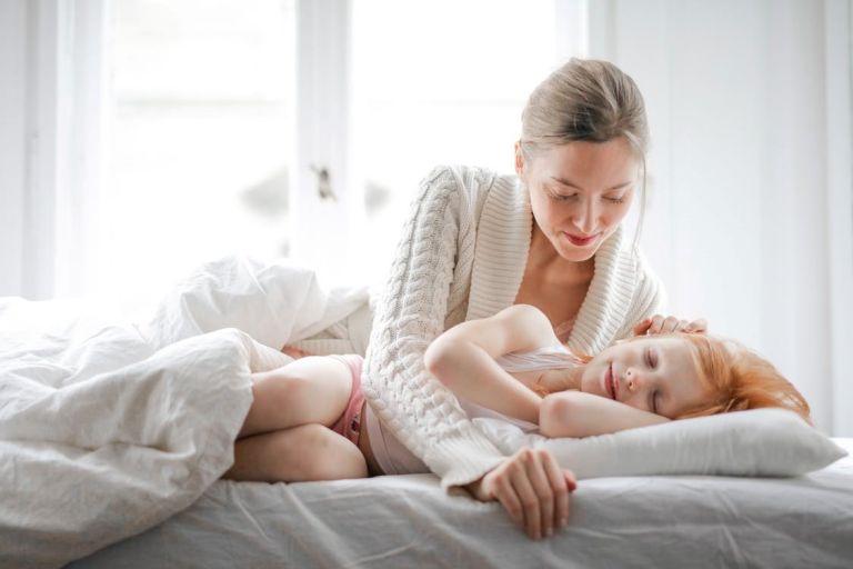 Äiti silittelee sängyssä nukkuvaa nukkuvaa lasta.
