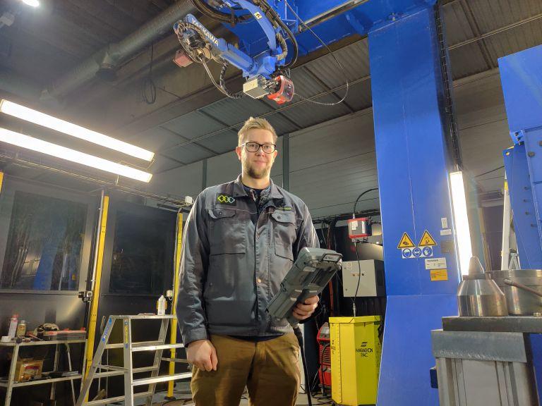 Mies seisoo teollisuushallissa. Taustalla nosturi.