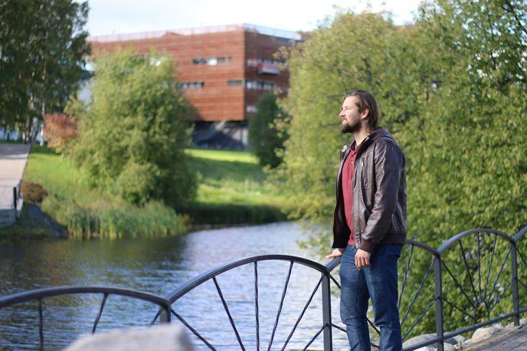 Mies nojaa kaiteeseen jokirannassa. Taustalla siintää SeAMKin kampuksen Frami F -rakennus.