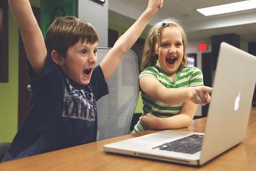 Kaksi lasta kannettavan tietokoneen ääressä.