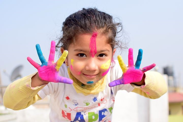 Lapsella on maalattu väreillä kasvot ja kädet.