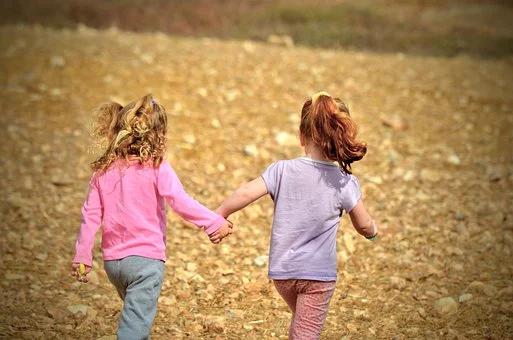 Kaksi lasta kulkee käsi kädessä.