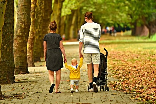 Perhe kävelyllä puistossa.