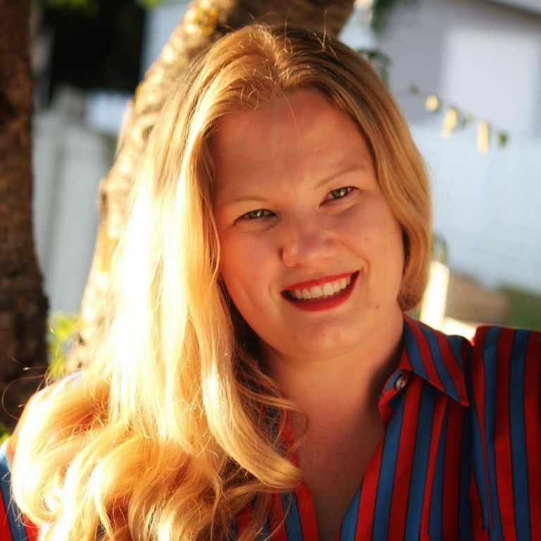 Vaaleahiuksinen nainen hymyilee.