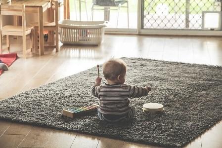 Pieni lapsi leikkii maton päällä.