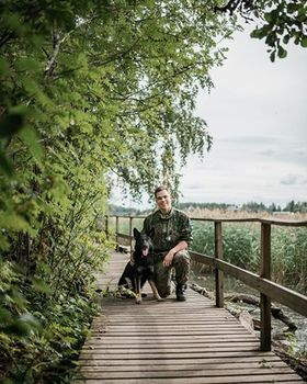 Nuori mies polviasennossa laiturilla koiran kanssa.