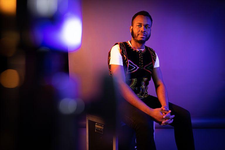 Nuori tumma mies istuu kädet ristissä katsoen kameraan.