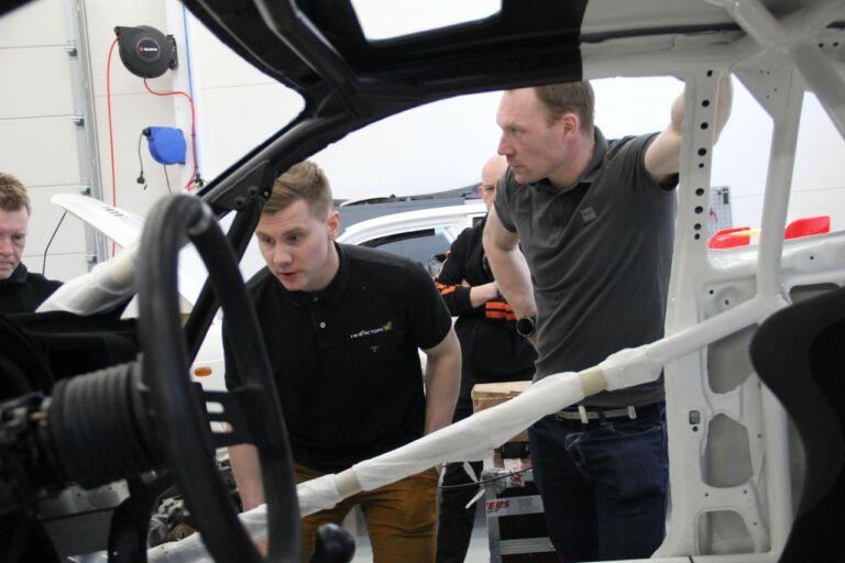 Kaksi miestä auton koria tutkimassa.