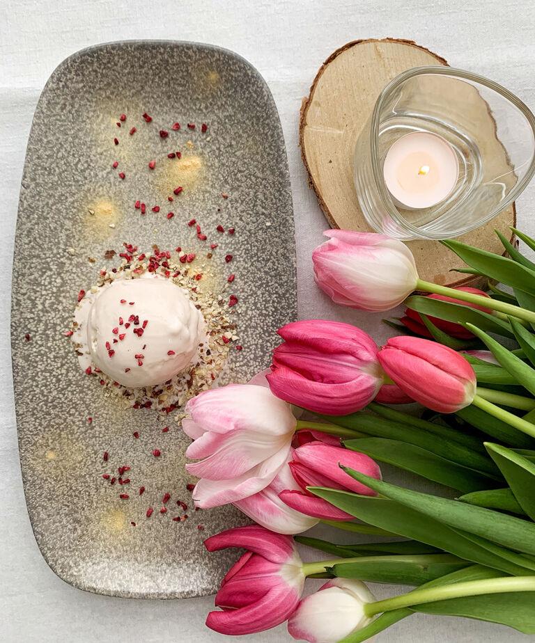 Kuva jäätelöannoksesta, vieressä kimppu tulppaaneita ja kynttilä.