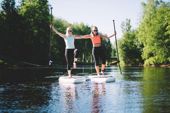Kaksi nuorta henkilöä sup-lautojen päällä joella./ Two young people on sup-boards on the river.