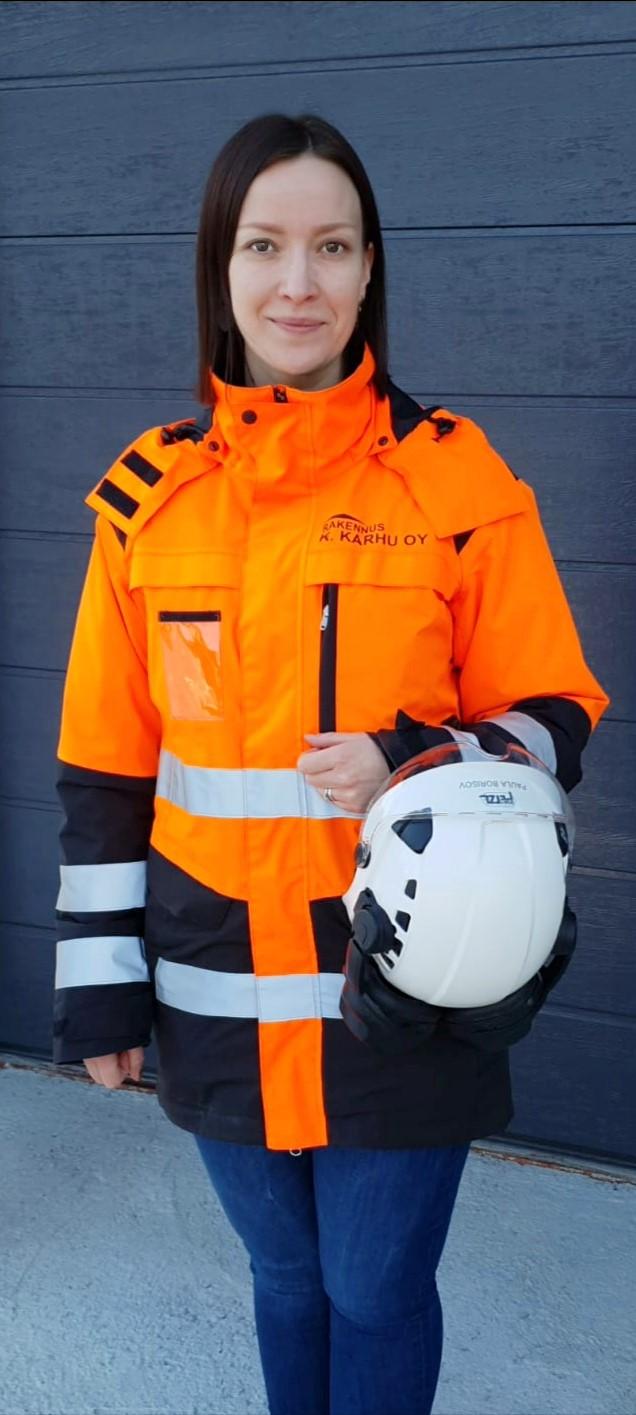 Tummahiuksinen nainen seisoo oranssi suojatakki päällään ja kypärä kädessään.