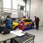 Opiskleijoita työskentelevät auton parissa auto- ja työkonetekniikan laboratoriossa.