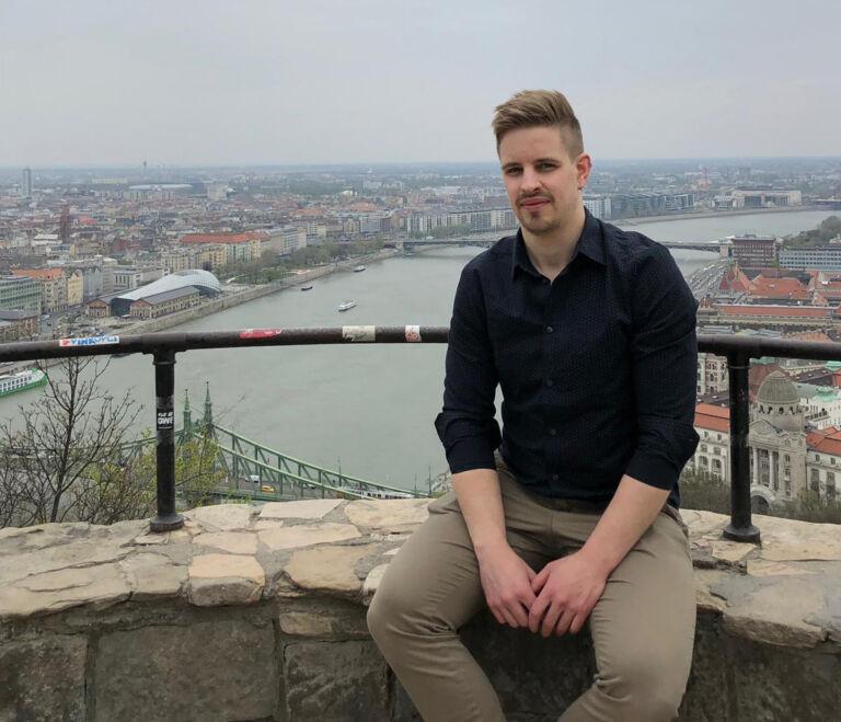 Henkilö istuu muurin päällä taustallaan joki ja kaupunkia.