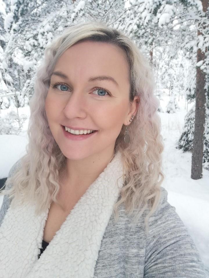 Vaaleahiukinen nainen talvimaisema taustallaan.
