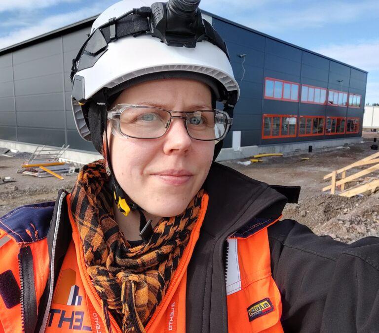 Nainen seisoo oranssi suojatakki päällään ja kypärä päässään teollisuushallin edessä.