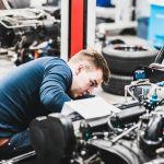 Opiskelija työskentelee auton parissa auto- ja työkonetekniikan laboratoriossa.