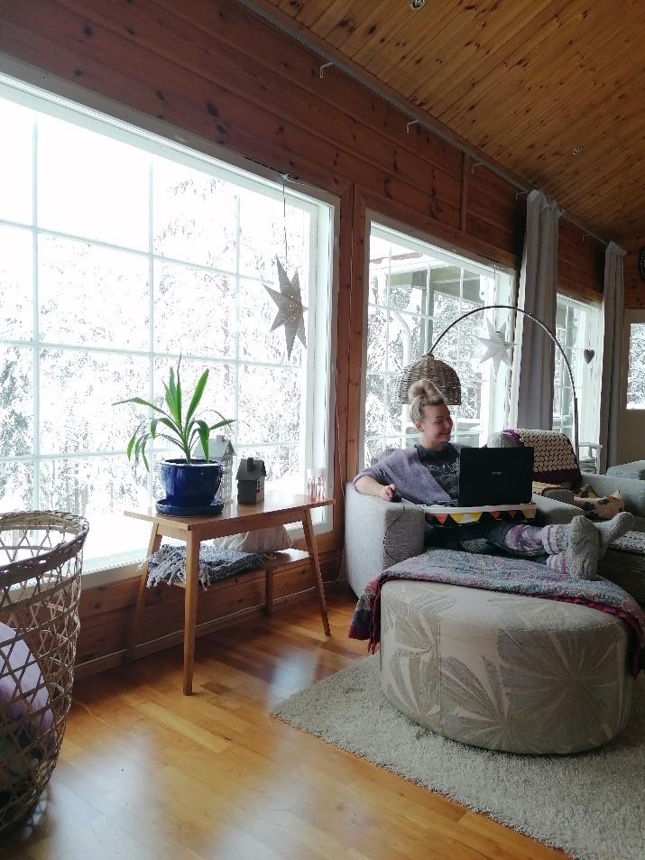 Henkilö istuu tietokone sylissään olohuoneen nojatuolissa.