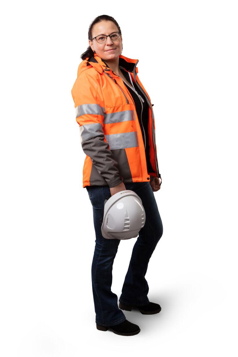 Tummahiuksinen nainen seisoo sivuttain kameraan oranssi suojatakki päällään ja kypärä kädessään.