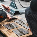 Kaksi henkilöä tutkii metallilevyjen hitsausjälkeä kone- ja tuotantotekniikan laboratoriossa.