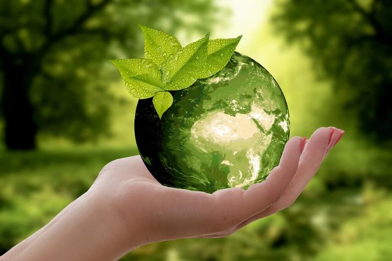 Käsi pitää ylhäällä lasista vihreäsävytteistä maapalloa. / A hand holding up a glass ball of green-toned planet Earth.