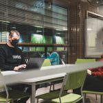 SeAMKin henkilöstöön kuuluvat mies ja nainen keskustelemassa yhdessä Frami F:n työskentelytilassa.