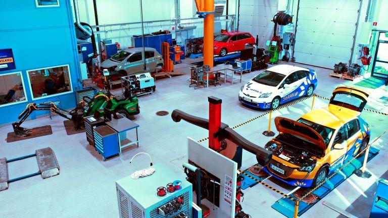 Auto-ja-työkonetekniikan laboratorio, jossa erilaisia laitteita ja koneita. Hallissa on myös muutama auto sisällä.