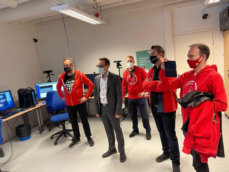 Joukko miehiä seisoo punaisissa huppareissa seuraamassa laitteen toimintaa. Yksi heistä kuvaa puhelimen kameralla.