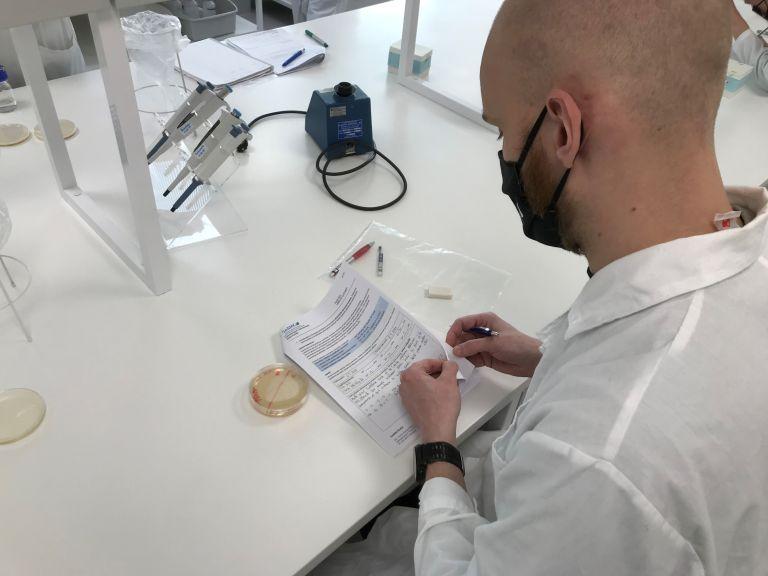 Mies kasvomaskissa ja valkoisessa takissa tutkii papereita laboratoriossa.tutki