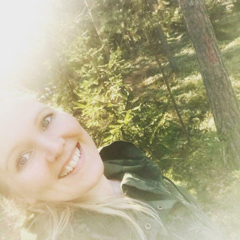 Vaalea nainen hymyilee taustallaan vihreä metsä.